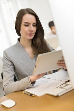 Pretty Business woman with tablet pc computer in her office